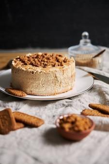 Disparo vertical de un delicioso pastel de galleta de loto con caramelo con galletas en la mesa