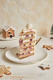 Disparo vertical de un delicioso pastel de navidad con adornos de pan de jengibre y bola de coco y almendra