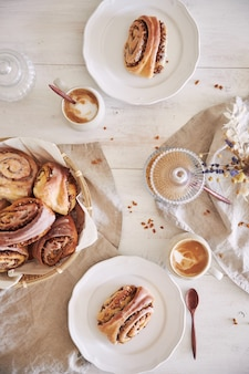Disparo vertical de deliciosos caracoles de nuez con café capuchino sobre mesa de madera blanca