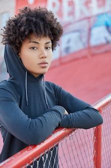 Disparo vertical de deportista seria tiene entrenamiento al aire libre en el patio de recreo, vestida con sudadera con capucha, se inclina sobre la valla