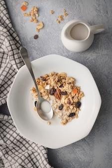 Disparo vertical de un desayuno oaten con frutos secos y frescos cerca de una jarra de leche