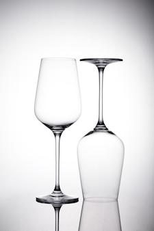 Disparo vertical de dos copas de vino vacías sobre la superficie blanca con sombras, uno está boca abajo
