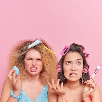 Disparo vertical de dos mujeres disgustadas que tienen prisa, prepárese para la fiesta, haga uso de herramientas cosméticas, cara sonriente, aplique rodillos, peine, pose de cabello, juntos, contra la pared rosa, con espacio de copia arriba
