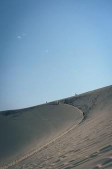 Disparo vertical de una duna de arena con gente caminando en la distancia y un cielo azul claro