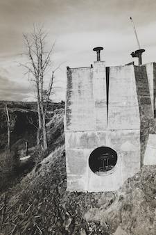 Disparo vertical de un edificio en la colina con un cielo nublado en el fondo en blanco y negro