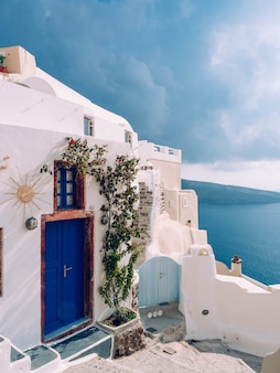 Disparo vertical de un edificio con una puerta azul en santorini, grecia