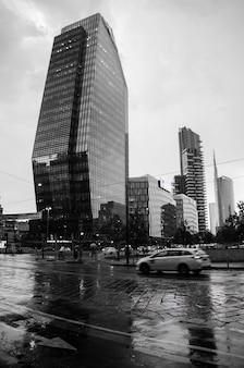 Disparo vertical en escala de grises de una calle con edificios modernos en milán, italia