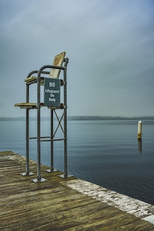 Disparo vertical de una estación de salvavidas en el muelle con un mar abierto y un cielo sombrío de fondo