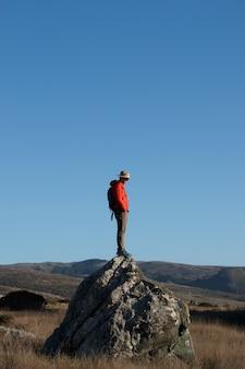 Disparo vertical de un excursionista masculino de pie sobre una piedra en las montañas