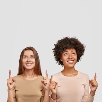 Disparo vertical de felices jóvenes hembras de raza mixta tienen sonrisas encantadoras, apuntan hacia arriba, están juntas contra la pared blanca