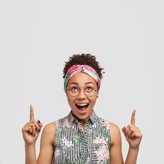 Disparo vertical de feliz joven mujer con cabello rizado, piel oscura y heathy, abre la boca, tiene una mirada alegre hacia arriba, puntos arriba