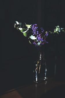 Disparo vertical de una flor morada en un frasco de vidrio con una pared oscura