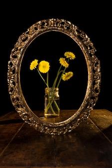 Disparo vertical de flores amarillas en un frasco de vidrio reflejado en el espejo