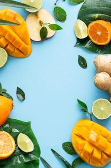 Disparo vertical de frutas cortadas sobre un fondo azul claro