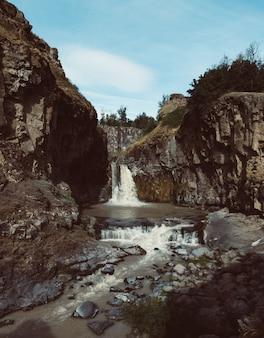 Disparo vertical de una fuerte cascada que fluye en el río entre enormes rocas