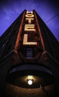 Disparo vertical de un gran edificio con un cartel de hotel y un cielo azul oscuro