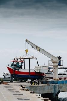 Disparo vertical de una grúa levantando un barco blanco en un muelle