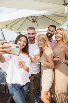 Disparo vertical de un grupo de jóvenes celebrando el verano en una fiesta en la azotea, tomando selfies con teléfonos inteligentes.