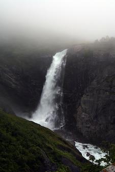 Disparo vertical de una hermosa cascada en las montañas envueltas con niebla en noruega