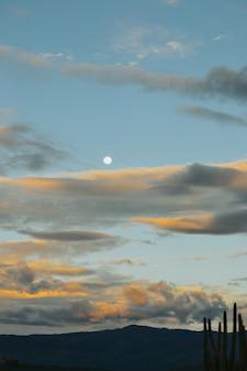 Disparo vertical de una hermosa luna con un cielo nublado