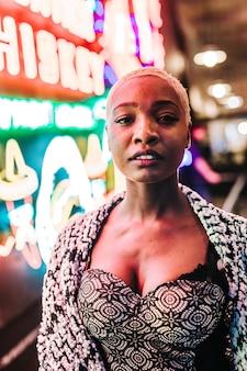 Disparo vertical de una hermosa mujer africana de pie cerca de luces de neón