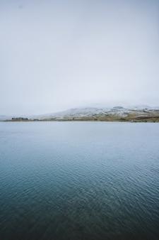 Disparo vertical de un hermoso lago rodeado de altas montañas en finse, noruega