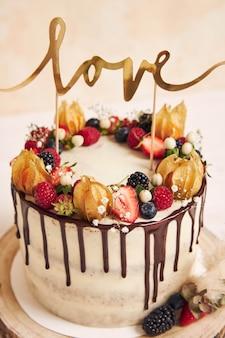 Disparo vertical de un hermoso pastel de bodas con goteo de chocolate de frutas y con adorno de amor