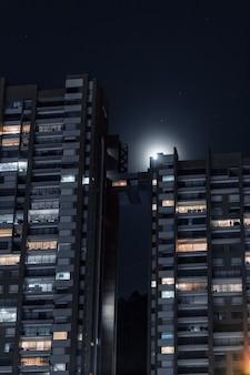 Disparo vertical de hermosos edificios de apartamentos conectados con un pequeño puente bajo el cielo estrellado
