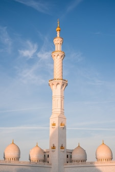 Disparo vertical de la histórica gran mezquita sheikh zayed en abu dhabi, emiratos árabes unidos contra el cielo azul
