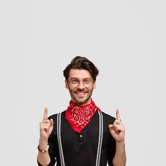 Disparo vertical de hombre barbudo feliz con expresión feliz apunta hacia arriba, viste camisa negra con pañuelo rojo, tiene una sonrisa amistosa, corte de pelo moderno, aislado sobre una pared blanca con espacio de copia arriba