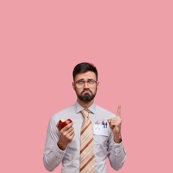 Disparo vertical de hombre infeliz con barba oscura, expresión facial negativa, come jugosa manzana, vestido con ropa formal, señala con el dedo índice hacia arriba