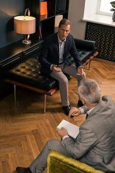 Disparo vertical de un hombre inquieto sentado en el sofá frente a su psicoanalista mientras comparte sus problemas psicológicos