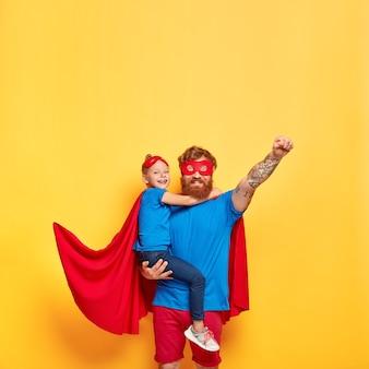 Disparo vertical de hombre pelirrojo fuerte en traje de superhéroe, levanta el puño y hace gesto de vuelo