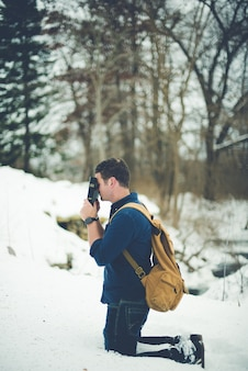 Disparo vertical de un hombre de rodillas en suelo nevado mientras sostiene la biblia contra su cabeza rezando