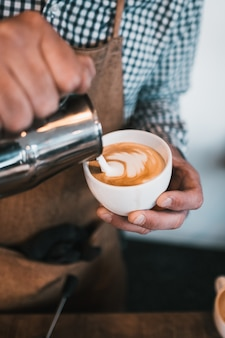 Disparo vertical de un hombre vertiendo leche en una taza de capuchino en un café