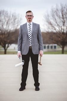 Disparo vertical de un hombre vestido con un traje mientras sostiene un martillo y un pincel en la calle