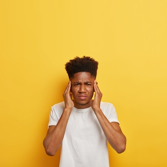 Disparo vertical de insatisfecho estudiante hombre de piel oscura mantiene las manos en las sienes, sufre de un terrible dolor de cabeza