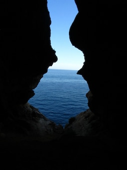 Disparo vertical desde el interior de la entrada de la cueva ghar in-naghag en las islas maltesas, malta