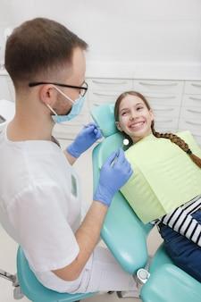 Disparo vertical de una joven alegre obteniendo sus dientes controlados por el dentista