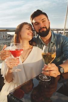 Disparo vertical de una joven pareja feliz riendo, disfrutando del vino en la terraza del bar