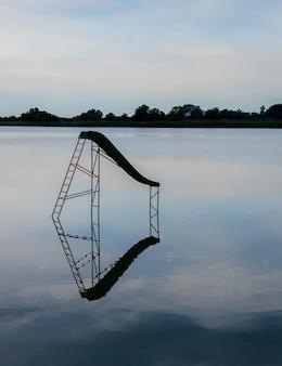Disparo vertical de un lago con un columpio de agua reflejada en el agua y árboles en el fondo
