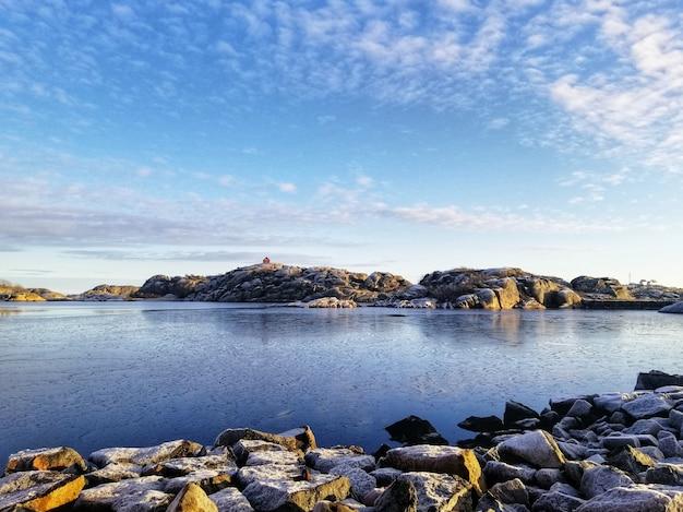 Disparo vertical de un lago rodeado por formaciones rocosas en stavern noruega