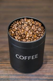 Disparo vertical de una lata negra con granos de café sobre una superficie de madera