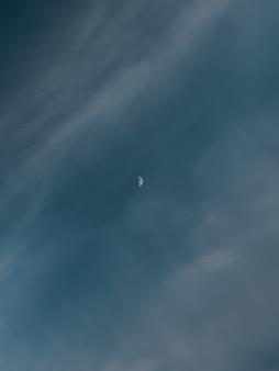 Disparo vertical de una luna creciente detrás de las nubes