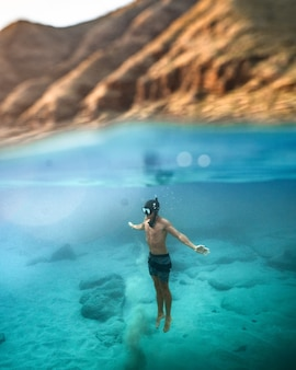 Disparo vertical de un macho de buceo en el mar turquesa