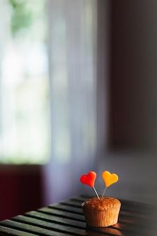 Disparo vertical de una magdalena con corazones de colores sobre ella