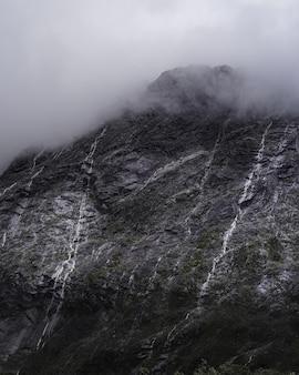 Disparo vertical de una majestuosa montaña con pequeñas cascadas en un clima brumoso