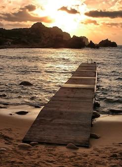 Disparo vertical de un malecón en la playa con la hermosa puesta de sol