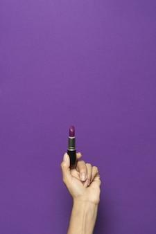 Disparo vertical de una mano sosteniendo un lápiz labial aislado sobre un fondo violeta
