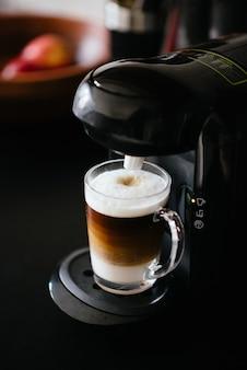 Disparo vertical de una máquina para hacer café haciendo un nescafé en un vaso